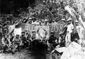 Che con combatientes de la Columna 4 posan alrededor de una bandera colocada en El Hombrito, 1957
