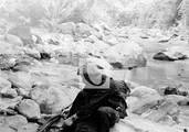 Che arreglando un fusil a orillas del río Ñacahuazú