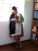 Mujer indígena boliviana leyendo Che Guevara Presente en una biblioteca comunitaria
